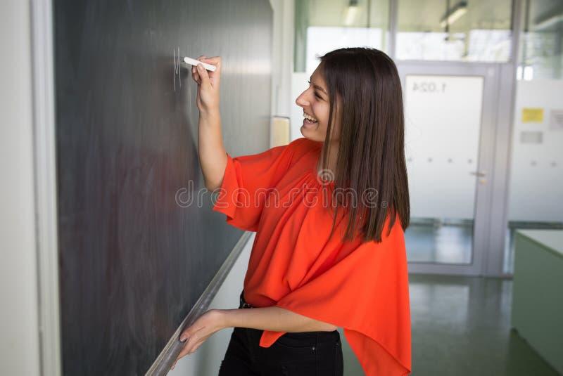 Ganska, unga studenter som skriver på kritan/svarta tavlan arkivbilder