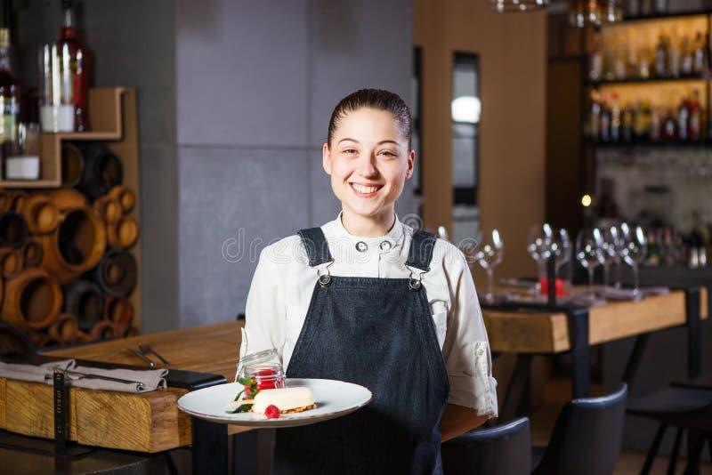 Ganson, de ambtenaren, mooie deushka met een glimlach en het verzamelde haar in werkende vormschort keuren een orde in restaurant royalty-vrije stock foto