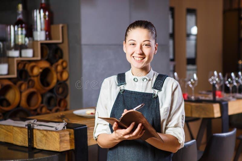 Ganson, de ambtenaren, mooie deushka met een glimlach en het verzamelde haar in werkende vormschort keuren een orde in restaurant royalty-vrije stock fotografie