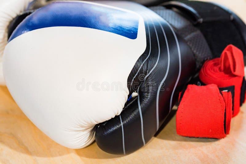 Gant de boxe noir, bleu et blanc sur le fond clair photo stock