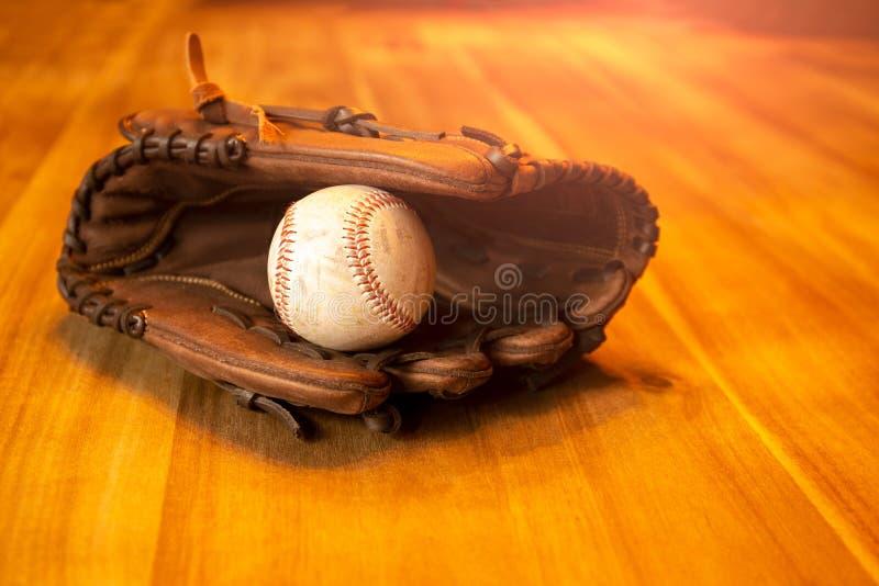 Gant de receveur de base-ball avec la boule sur la table en bois photographie stock libre de droits
