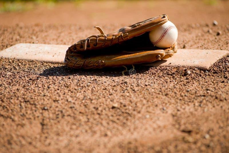 Gant et bille de base-ball sur le monticule de pichet photographie stock libre de droits