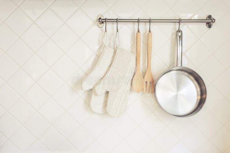 Gant et Pan Wooden Spoon d'ustensile de cuisine sur le mur de tuiles photos libres de droits