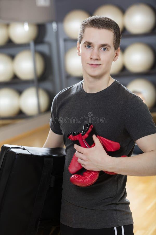 Gant et sac de boxe de transport d'homme dans le gymnase photographie stock libre de droits