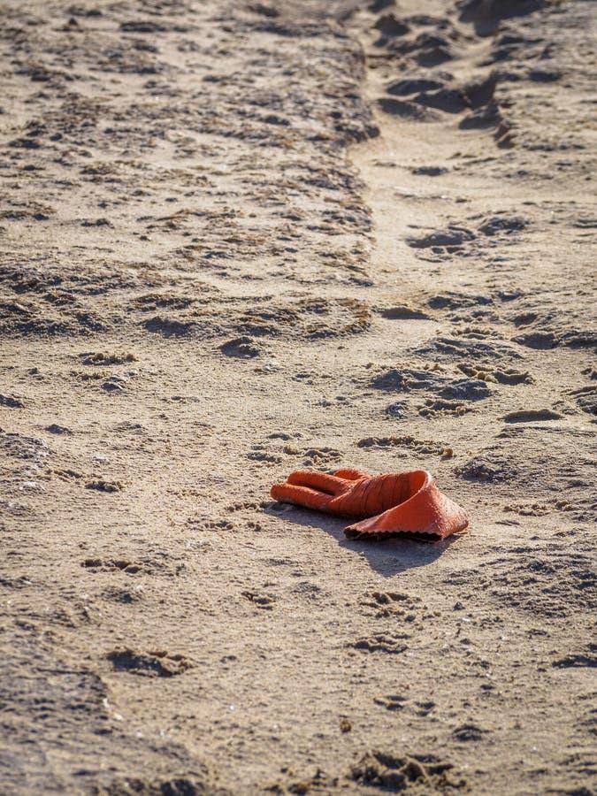 Gant orange abandonné sur la plage au coucher du soleil photo stock