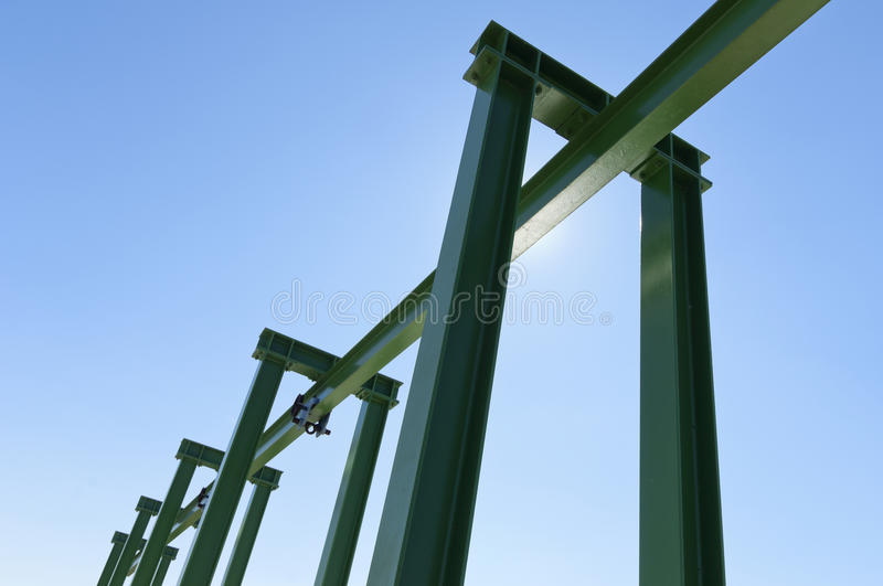 Gantry crane. Detail of a small gantry crane painted green against the blue sky royalty free stock photos