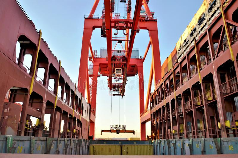 Gantry crane loading containers on the cargo ship. Gantry crane is loading containers on the container ship, view on the crane and open cargo hold stock photography