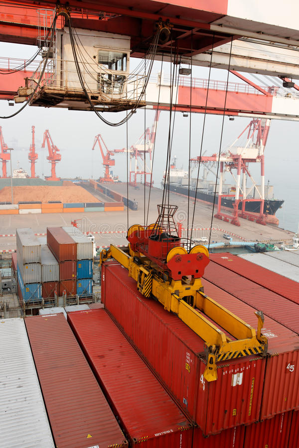 Gantry crane loads container onto freighter ship. A gantry cranes loads or unloads a 45 foot shipping container from a freighter ship berthed at the Port of royalty free stock image