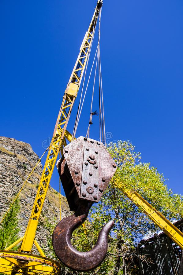 The gantry of a quarry. A yellow gantry on a background blue sky in the abandoned marble quarry near Moncenisio dam Italy stock image