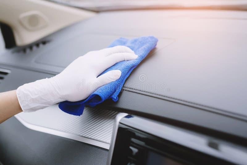 Gants d'usage d'homme de travailleur nettoyant la console intérieure de voiture avec le tissu de microfiber, détaillant, service  photos libres de droits