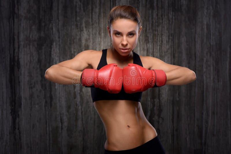 Gants de boxe de port de femme sportive de métis photo stock