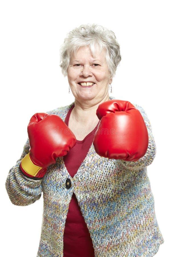 Sourire de port de gants de boxe de femme supérieure images libres de droits