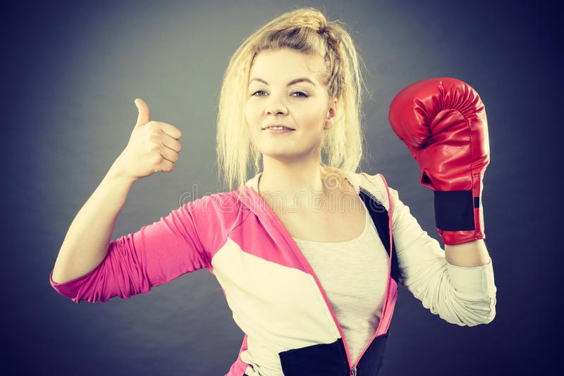 Gants de boxe de port de femme montrant le pouce  image libre de droits