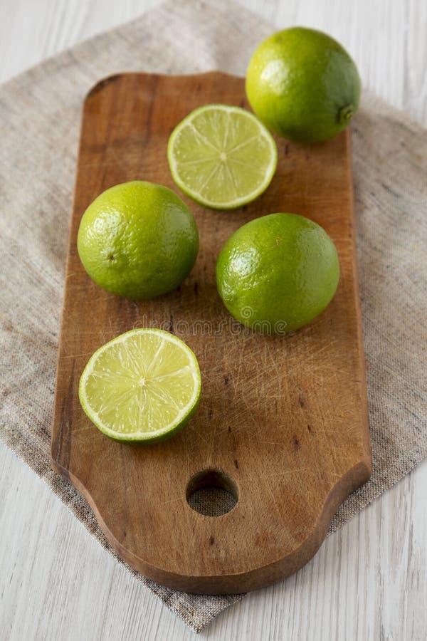 Ganz- und Schnittgrünzitrusfruchtkalke auf einem rustikalen hölzernen Brett über weißer Holzoberfläche, Seitenansicht Nahaufnahme stockfoto