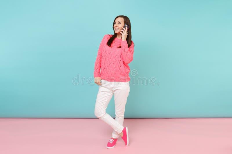 Ganzaufnahme der Frau in gestrickter rosafarbener Strickjacke, weiße Hosen sprechend am Handy lokalisiert auf hellem rosa Blau stockfoto