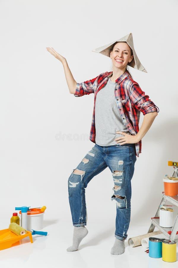 Ganzaufnahme der Frau in der Zeitungshutstellung nahe Instrumenten für das Erneuerungswohnungshaus lokalisiert auf Weiß lizenzfreies stockfoto