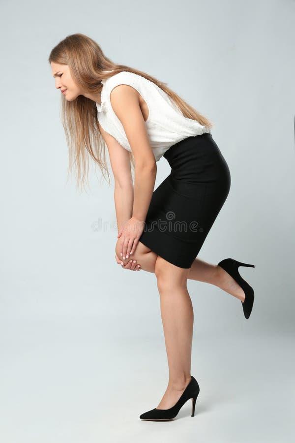 Ganzaufnahme der Geschäftsfrau, die Knieprobleme auf Grau hat lizenzfreies stockfoto