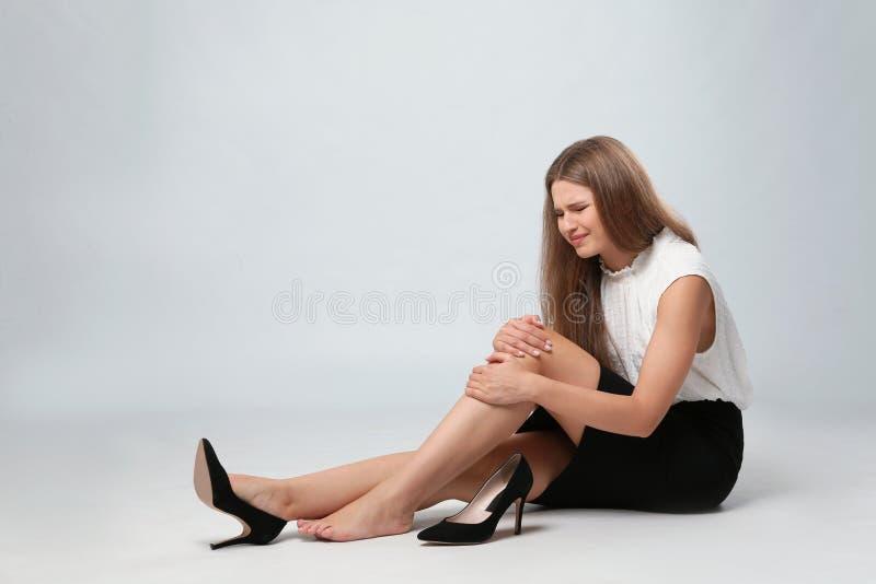 Ganzaufnahme der Geschäftsfrau mit den Knieproblemen, die auf Grau sitzen lizenzfreies stockbild
