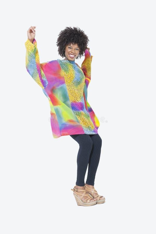 Ganzaufnahme der glücklichen Afroamerikanerfrau im dashiki, das über grauen Hintergrund tanzt stockfotografie