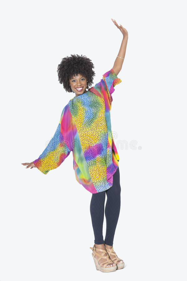 Ganzaufnahme der glücklichen Afroamerikanerfrau im dashiki, das über grauen Hintergrund tanzt lizenzfreies stockbild