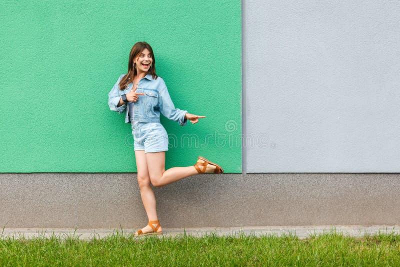 Ganzaufnahme der glücklichen aufgeregten Schönheit in der zufälligen Jeansdenimart in der Sommerzeit, die nahe Grünem und hellbla stockfotos