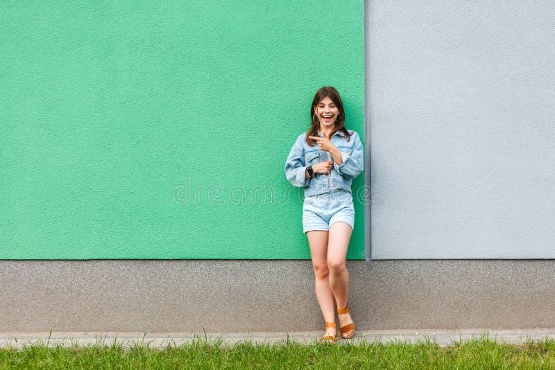 Ganzaufnahme der glücklichen aufgeregten Schönheit in der zufälligen Jeansdenimart in der Sommerzeit, die nahe Grünem und hellbla stockfotografie