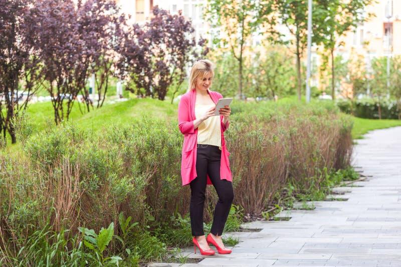 Ganzaufnahme der glücklichen schönen jungen erfolgreichen Bloggergeschäftsfrau in der Eleganzart, die auf grünem Park, halten ste stockfoto