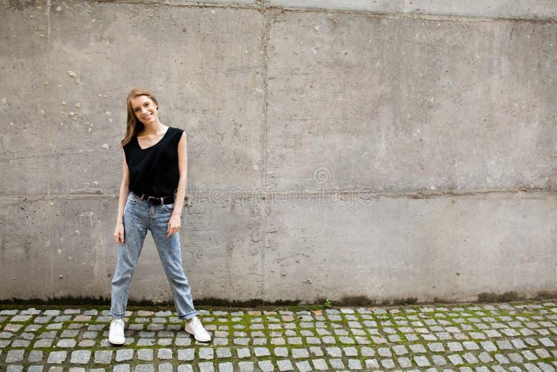 Ganzaufnahme der jungen lächelnden Frau, die gegen graue Wand steht stockfotos