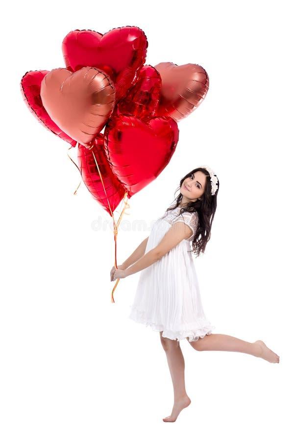 Ganzaufnahme der netten jungen Frau im weißen Kleid mit den roten Heliumballonen lokalisiert auf Weiß lizenzfreie stockfotos