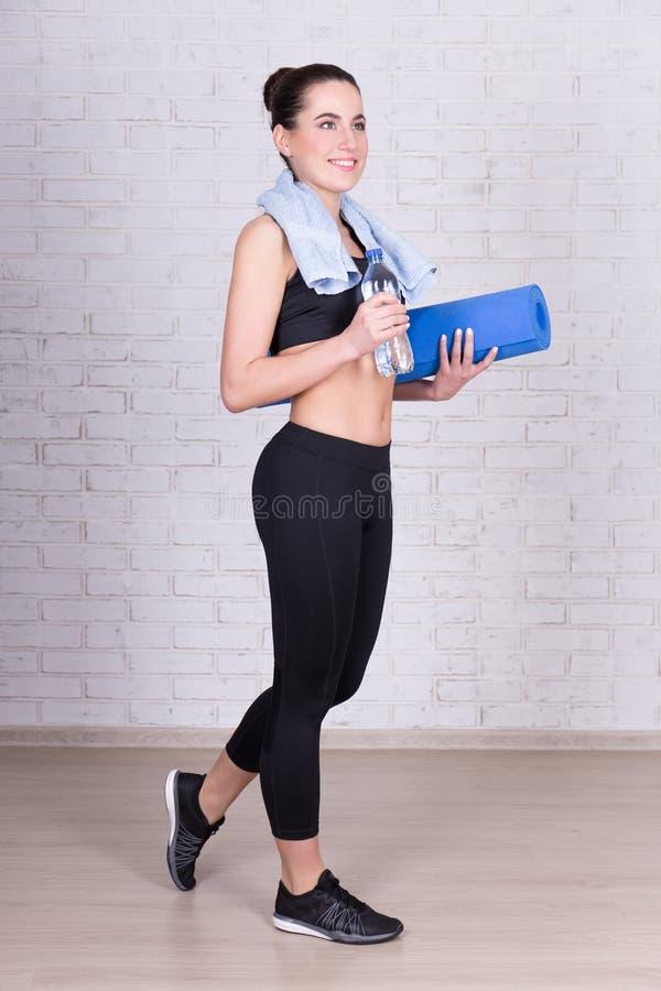 Ganzaufnahme der schönen dünnen Frau mit Yogamattenstand stockfotografie