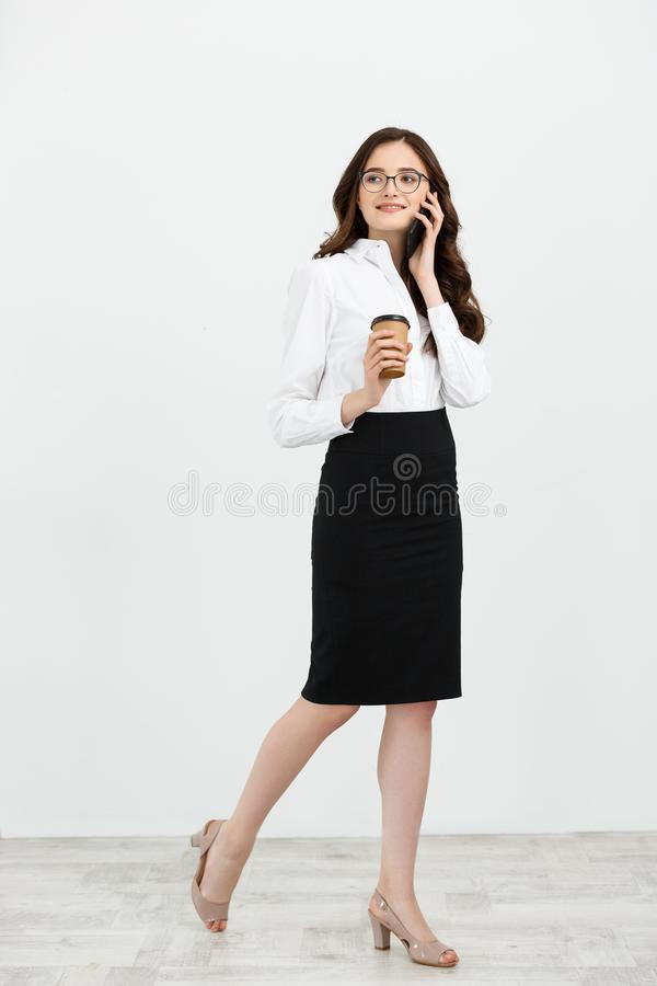 Ganzaufnahme der schönen jungen Geschäftsfrau in der formellen Kleidung gehend und für Handy mit Takeaway sprechend lizenzfreies stockbild