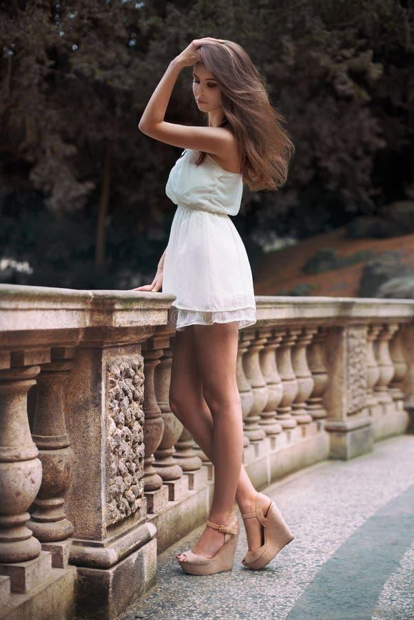 Ganzaufnahme der schönen vorbildlichen Frau mit den langen Beinen, die das weiße Kleid aufwirft oudoors tragen stockbild