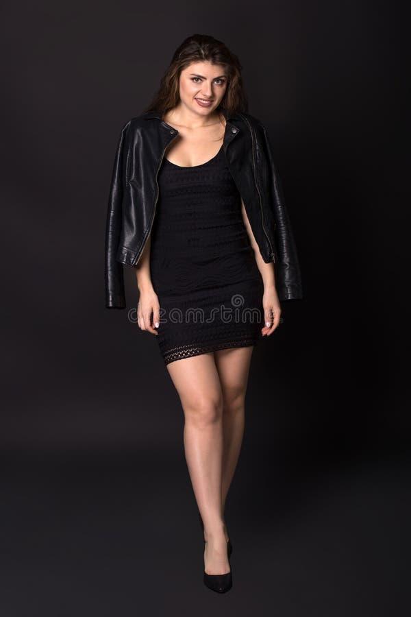 Ganzaufnahme der sexy kaukasischen jungen Frau in der Lederjacke und im kurzen schwarzen Kleid, werfend über schwarzem Hintergrun lizenzfreies stockfoto