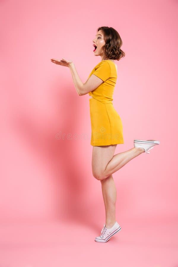 Ganzaufnahme der spielerischen attraktiven Frau im gelben Kleid stockbild