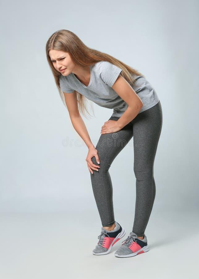 Ganzaufnahme der Sportlerin, die Knieprobleme auf Grau hat lizenzfreie stockbilder