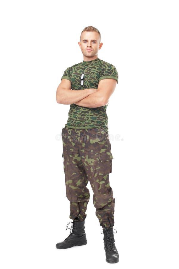 Ganzaufnahme des ernsten Armeesoldaten mit seinen Armen kreuzen stockfotos