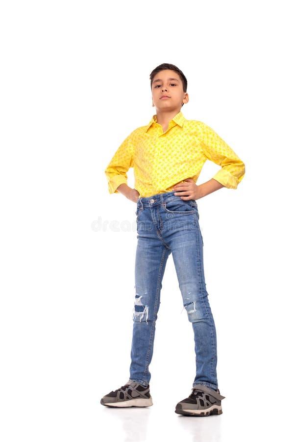 Ganzaufnahme des ernsten Jungen des Brunette mit den Armen auf den Hüften, die gelbes Hemd und Jeans auf einem weißen Hintergrund lizenzfreies stockbild