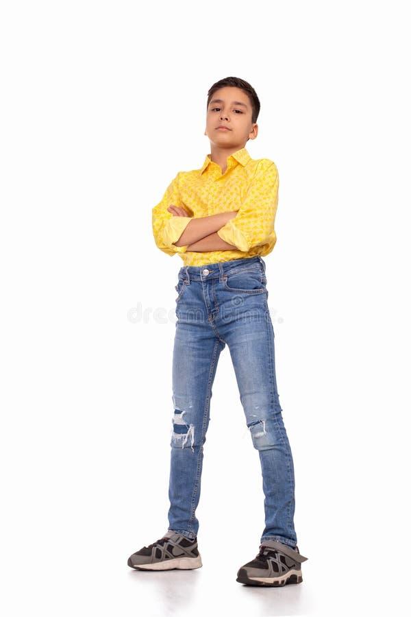 Ganzaufnahme des ernsten Jungen mit Arme gekreuztem tragendem gelbem Hemd und Jeans auf einem Weiß stockfoto