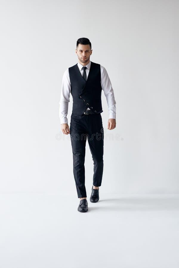 Ganzaufnahme des Gehens des eleganten Mannes in der Klage auf wei?em Hintergrund lizenzfreies stockfoto