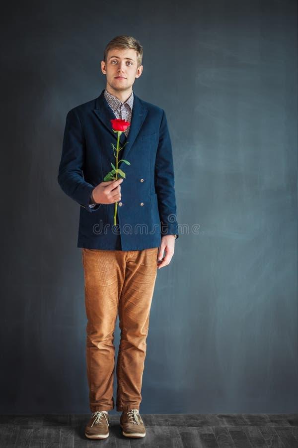 Ganzaufnahme des glücklichen gutaussehenden Mannes mit Rotrose stockfotografie