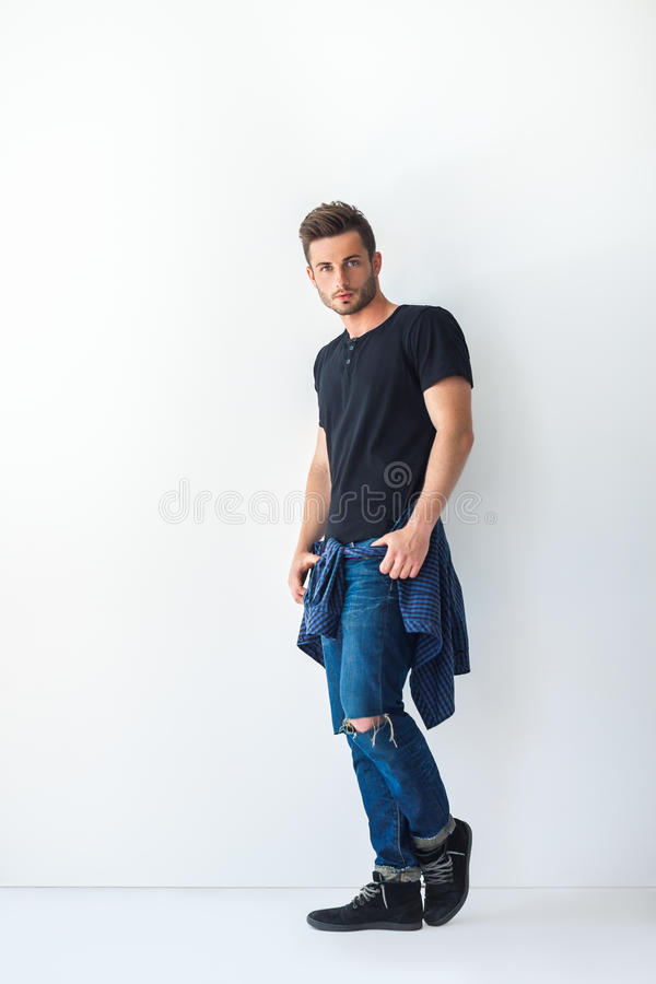 Ganzaufnahme des hübschen stilvollen Mannes, der am weißen wa sich lehnt lizenzfreies stockfoto