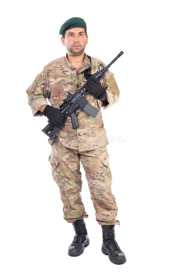 Ganzaufnahme des jungen Mannes in der Armee kleidet das Halten eines weap lizenzfreie stockfotos