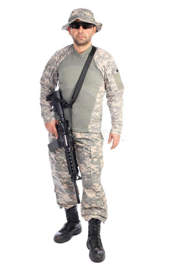 Ganzaufnahme des jungen Mannes in der Armee kleidet das Halten eines weap stockbild