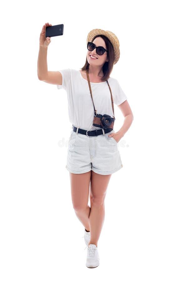 Ganzaufnahme des jungen Schönheitstouristen im Strohhut, der selfie Foto mit dem Smartphone lokalisiert auf Weiß macht lizenzfreies stockfoto