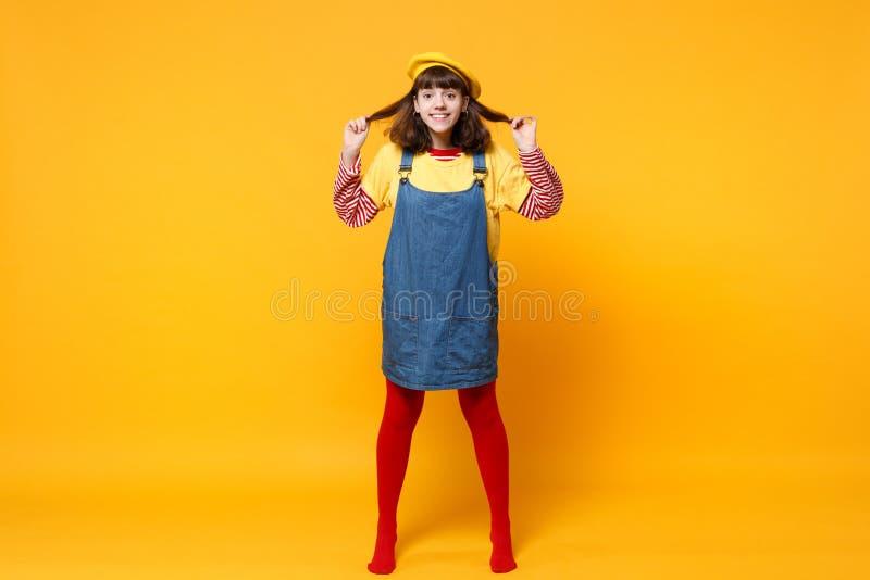 Ganzaufnahme des lustigen Mädchenjugendlichen in französischen Barett und Denim sundress, die Haar lokalisiert auf gelber Wand ha stockbild