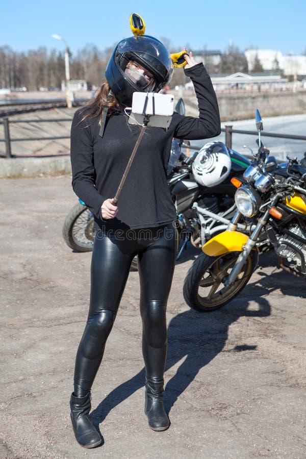 Ganzaufnahme des Mädchenradfahrers mit dem Smartphone angebracht an selfie Stock, gegen das Fahrrad schießend stockfotografie