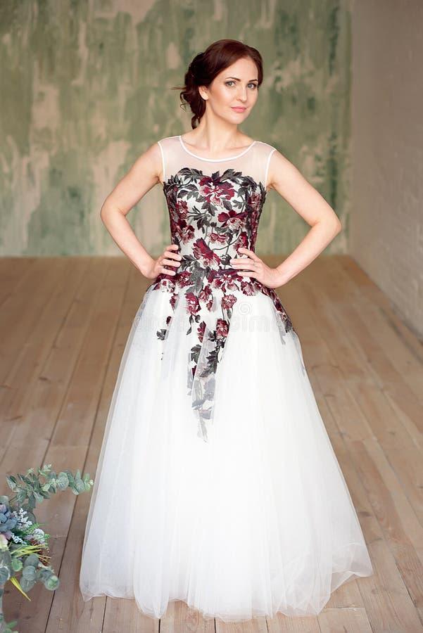 Ganzaufnahme des schönen luxuriösen weiblichen Modells mit dem Mittelbraunhaar in einem langen fashinable Kleid, das herein steht lizenzfreie stockfotografie