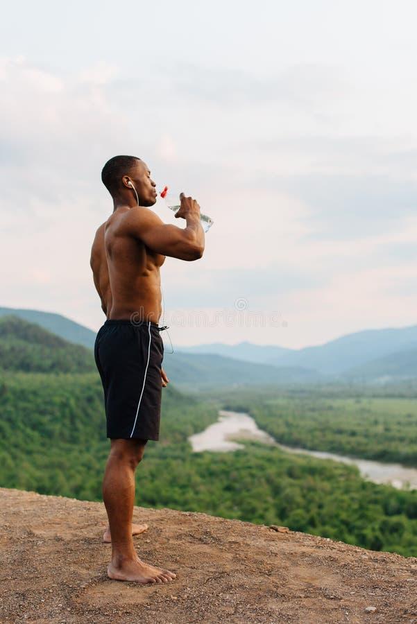 Ganzaufnahme des Trinkwassers des muskulösen Mannes des Afroamerikaners nach der Sportausbildung Atemberaubender grüner Berg stockbilder