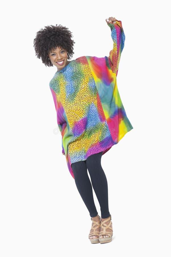 Ganzaufnahme einer Afroamerikanerfrau im dashiki, das über grauem Hintergrund steht lizenzfreies stockfoto