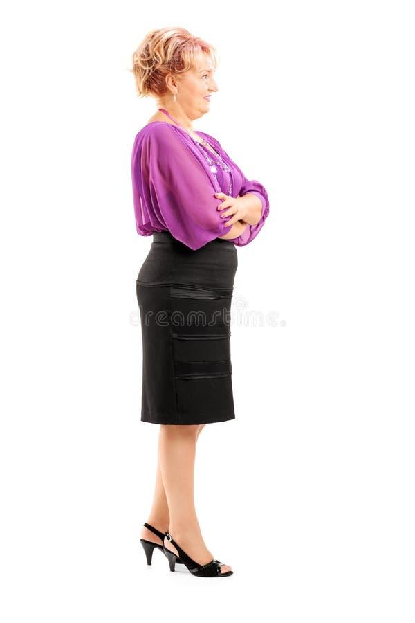 Ganzaufnahme einer blonden reifen Frau, die in Linie wartet stockfoto
